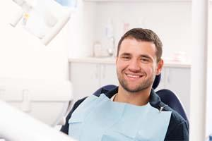 Man sitting in dental exam chair l Shipp Family Dentistry