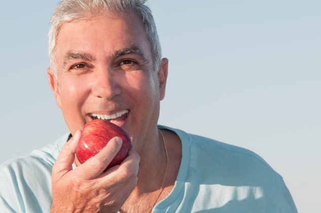 Man Eating An Apple | Columbus MS | Dental Crowns